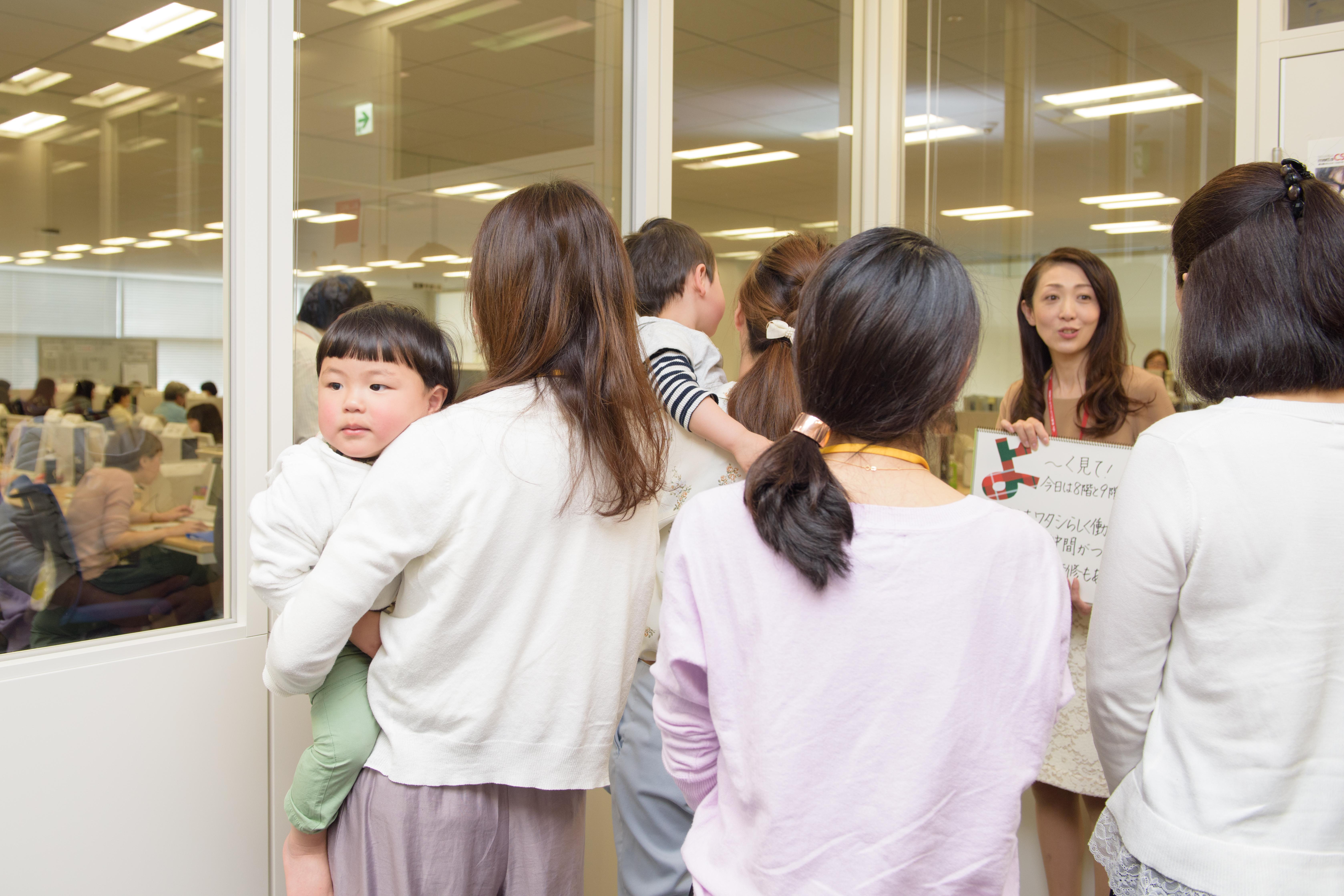 説明会で見学をする参加者たち。子どもを抱っこする参加者の姿も。
