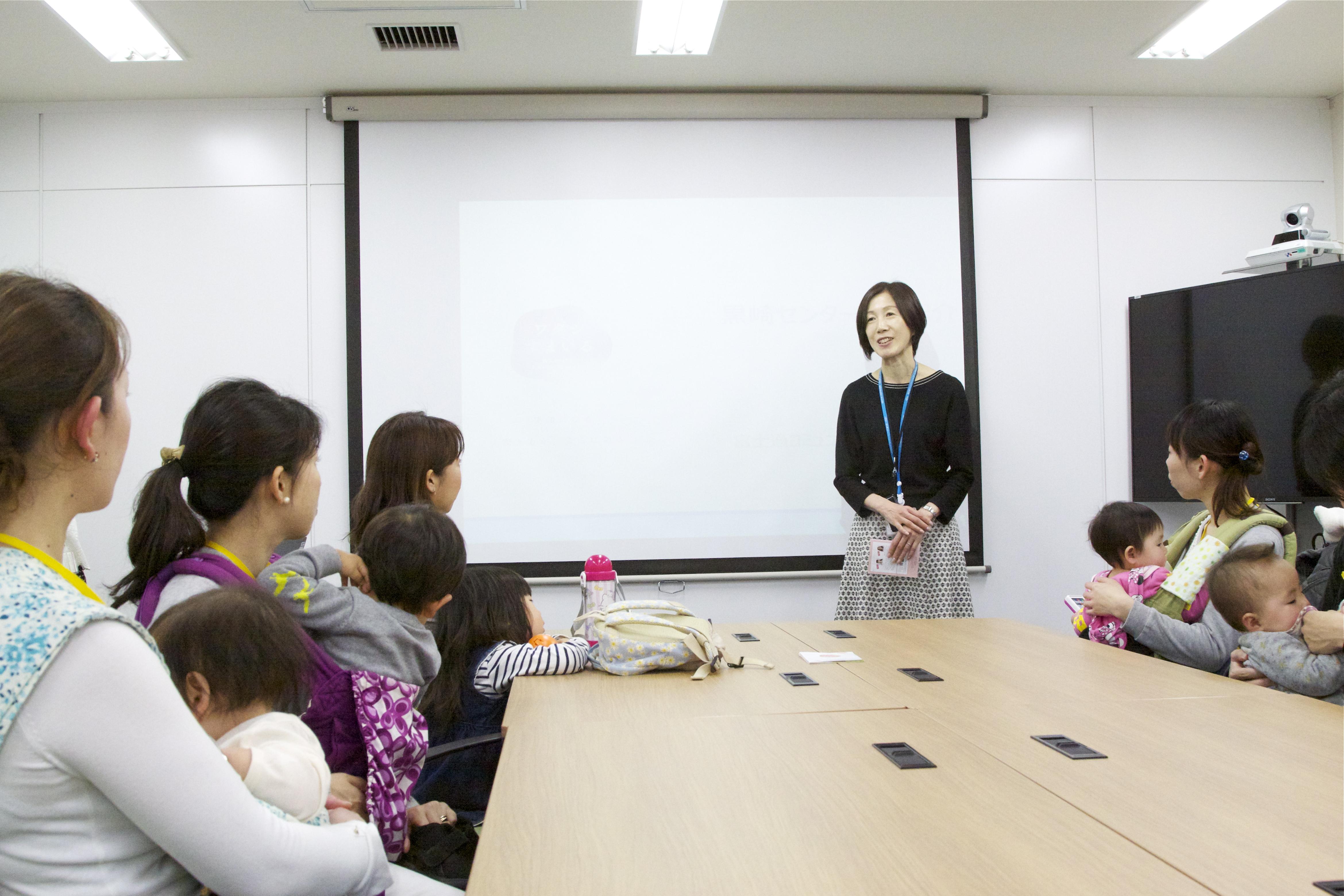 赤ちゃんと一緒に説明会で話をきく参加者たち