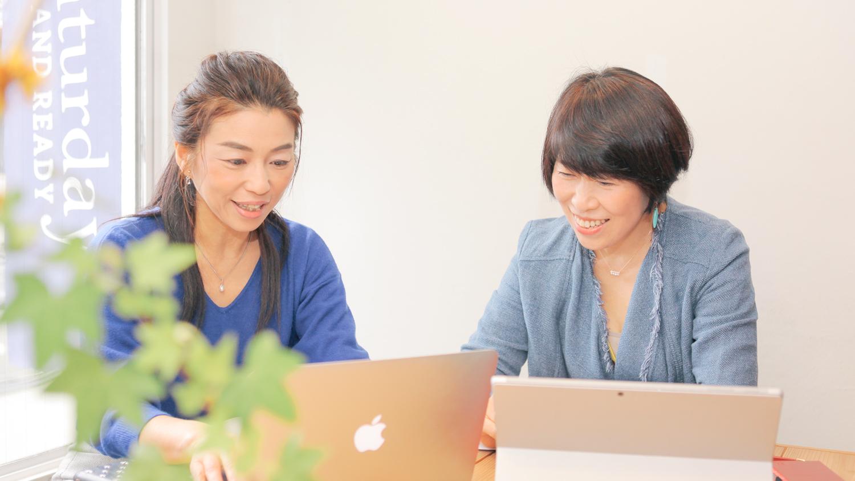 パソコンを見ながら楽しそうに仕事をする寺島と阿部
